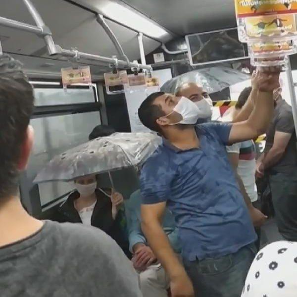 Metrobüste tavandan akan suya karşı şemsiye açtılar